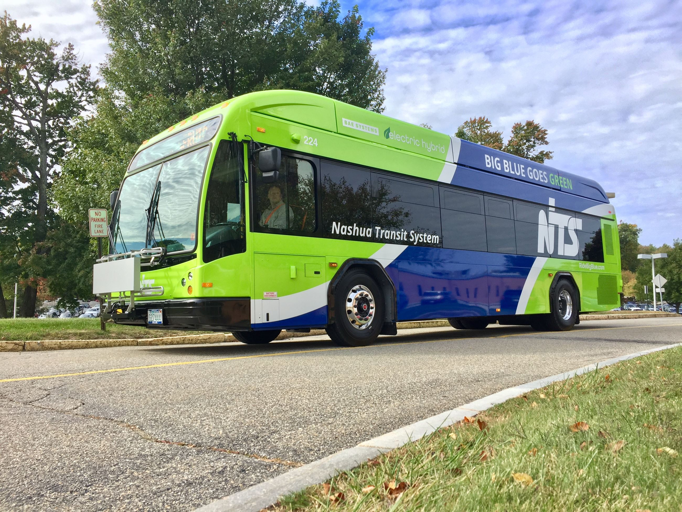NTS's new lime green and blue electric hybrid bus pulls up the driveway at BAE Systems
