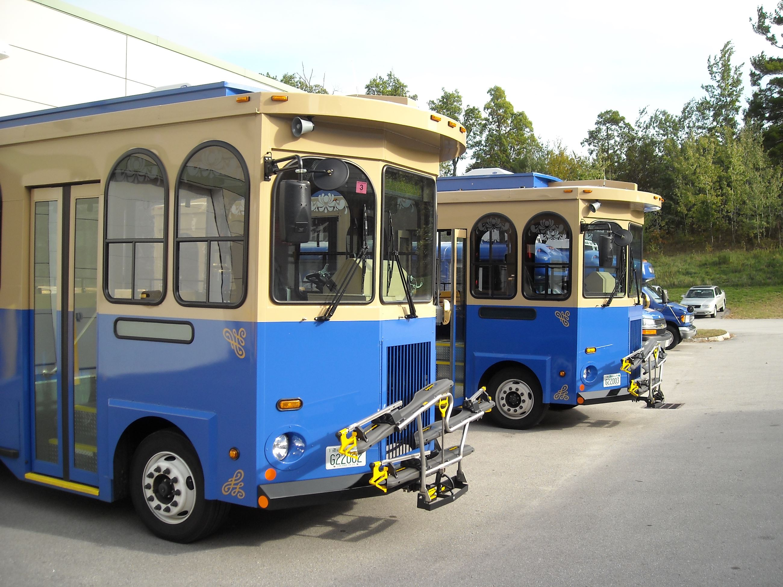 2 blue and gold trolleys sit outside of the Nashua Transit System garage